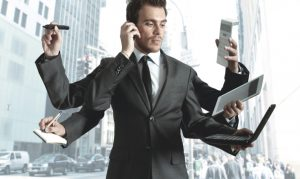 A man in a suit with 3 pairs of arms holding something in each: a pen, a phone, a notebook, etc