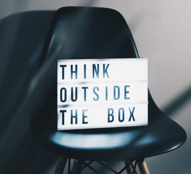 Think outside the box sign on a chair