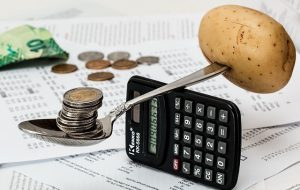 A spoon balanced on a calculator by a pile of coins on one side and a potato on the other
