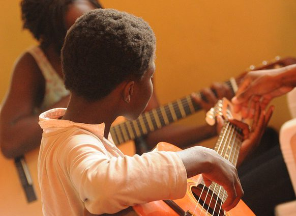 A black boy learning to play guitar
