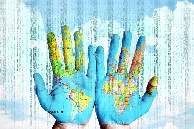 Hands painted with the world map; clouds in the background; unreadable digital text running across the image.