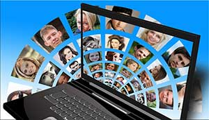 The main purpose for blogging is to reach more people -- laptop and photos of many people.