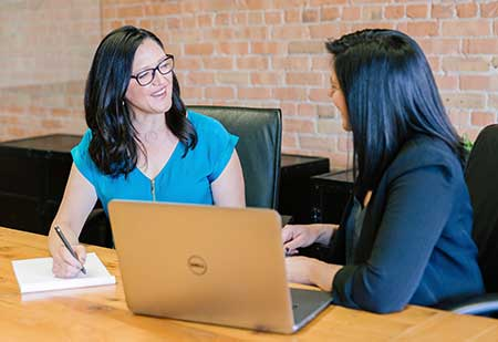 Two ladies by the desk with a laptop are engaged in conversation.