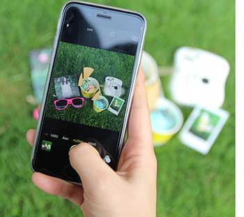 A hand with a smartphone taking a photo of objects on the grass.